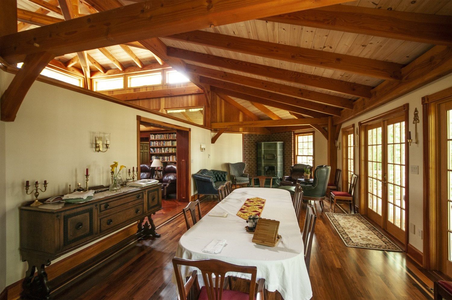 The reading nook at the far end of the dining room features a soap stone wood burner.